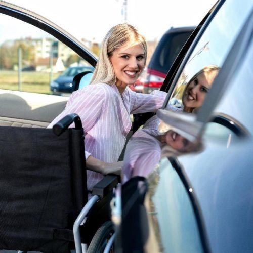 mujer en silla de ruedas entrando en su coche